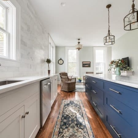 white kitchen remodel with blue island and marble counter tops